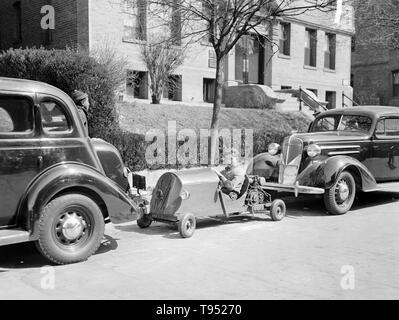 """Mit dem Titel: """"Washington Youngster löst Parkplatz Problem."""" Transport und keine Parkplätze Sorgen. Nelm Clark, 16 Jahre alte Washington Knabe, lösen dieses Problem durch die Kombination von einem Rasenmäher motor mit einem Motorrad die Gänge dieser ungewöhnlichen midget Auto zu machen. Kostet 60 $ die Neuerfindung zu bauen wiegt nur 150 Pfund - das Gewicht ist seine Besonderheit - und wenn Sie laufen aus Gas Sie es leicht schieben oder unter dem Arm zu verstauen und nach Hause gehen. Washington, D.C. fotografiert von Harris & Ewing März 30, 1937. Stockbild"""