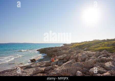 Cap de Ses Salines, Mallorca, Spanien - August 2016 - Touristen sitzen am einsamen Strand von Ses Salines genießen den Sonnenuntergang Stockbild