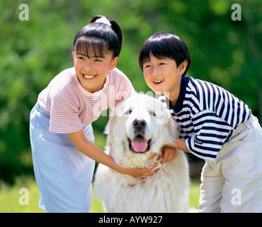 Jungen und Mädchen mit großen weißen Hund Stockbild