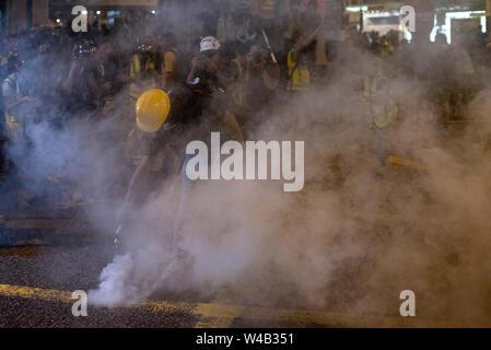 Eine Demonstrantin rauschenden Wasser in ein tränengaskanister von der Polizei in ein Versuch, sie zurück zu der Polizei zu werfen gefeuert zu setzen. Die Hong Kong Polizei hat verwendet, Tränengas und Blase Munition gegen Demonstranten als Hunderte von Demonstranten marschierten hat die geplante Demonstration Route. Zehntausende von pro-demokratischen Demonstranten haben wöchentliche Kundgebungen auf den Straßen von Hong Kong gegen die umstrittene Auslieferung Rechnung seit Anfang Juni fortgesetzt Stockbild