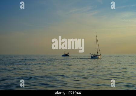 Ein Segelboot und ein Motorboot auf dem offenen Meer im Abendlicht. Ein Segelboot und Motorboot auf dem offenen Meer im Abendlicht. Stockbild