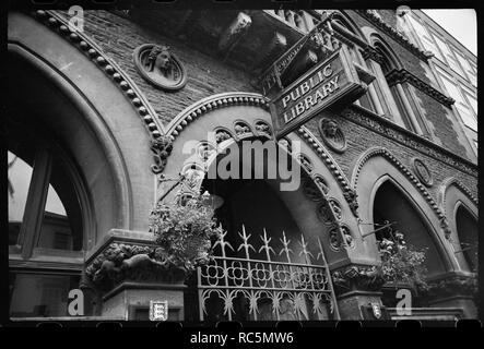 Bibliothek, Museum und Kunstgalerie, Broad Street, Hereford, Herefordshire, c 1955 - c 1980 detaillierte Ansicht der vorderen Fassade der öffentlichen Bibliothek, mit dem schmiedeeisernen Tor Eingang, runden Nischen mit Büsten und der Balkon auf der ersten Etage. Das Bild zeigt einen Teil des Erdgeschosses Arcade, die Hauptstädte mit Schnitzereien von Pflanzen und Tieren angereichert, und konzentriert sich auf den zentralen Arch, mit halbrunden Nischen auf die Fassade und die Schattenseite der Arch, mit Schnitzereien von verschiedenen Tieren in jedem. Unter dem Bogen ist ein schmiedeeisernes Tor, und über der zentralen Arch, auf beiden Seiten, Stockbild