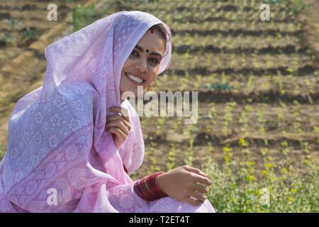 Nahaufnahme eines Jungen lächelnd ländliche Frau sitzt in ihrer Landwirtschaft Feld über dem Kopf mit Sari. Stockbild