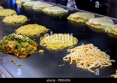 Okonomiyaki wird auf einer großen Bratpfanne, Hiroshima, Japan, Asien vorbereitet Stockbild