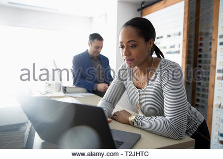 Weibliche Innenarchitekt mit Laptop im Design Studio Stockbild