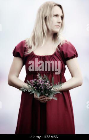 eine Frau in einem roten Kleid mit einem Blumenstrauß Stockbild