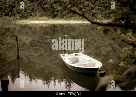Eine verkettete Ruderboot schwimmt auf einem See Stockbild
