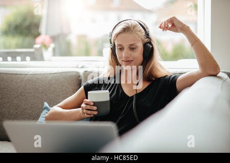 Schöne junge Frau mit Kopfhörern hält eine Tasse Kaffee und Blick auf Laptop. Frau sitzt auf der Stockbild