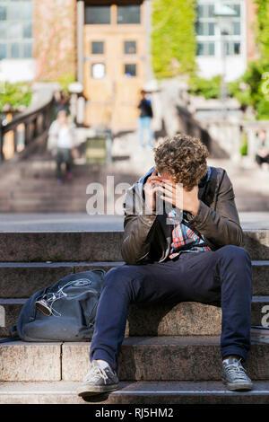 Junger Mann an einer Haustür sitzen Stockbild