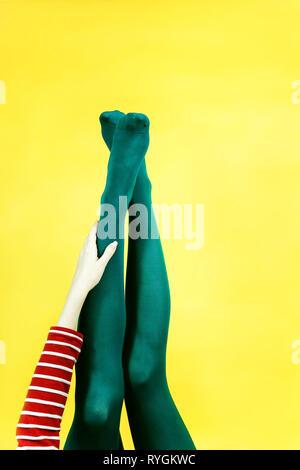 Pop Art Stück junge Frau Beine in Strumpfhosen auf gelbem Hintergrund Stockbild