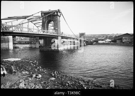 Alte Scotswood Brücke, Gateshead, Tyne & Amp; Verschleiß, c 1955 - c 1967. Lokal bekannt als die Kettenbrücke, die alten Scotswood Brücke a Suspension Bridge wurde mit zwei großen steinernen Strompfeilern, von John Green entwickelt und im April 1831 eröffnet. Wenn der Vorgang abgeschlossen war es die erste Brücke über den Fluss Tyne auf Tyneside in der industriellen Ära errichtet werden. Die Brücke wurde 1967 abgerissen und durch eine neue Brücke, im Bau im Hintergrund ersetzt. Stockbild
