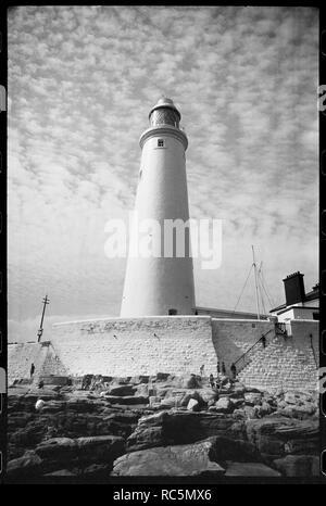 St Mary's Leuchtturm, Whitley Bay, North Tyneside, c 1955 - c 1980. Eine Außenansicht des 19. Jahrhunderts Leuchtturm, mit dem 126 m hohen Turm mit seitlichem Cottage der Keeper auf der rechten Seite, und ein Stein Mauer mit Treppe zu den komplexen und Leute saßen auf den Felsen, aus dem Osten gesehen. Der Turm der Leuchtturm ist ein weißes gerendert Tower 126 m hoch, mit Kuppeln Dach und weathervane. Die Fenster sind im gesamten Turm verstreut, und die Fenster der Laterne Zimmer an der Spitze haben diagonal Scheiben. Die wirtstochter Cottage unten ist eine steinerne Gebäude, weiß gestrichen und mit t Stockbild