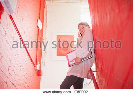 Lächelnde Geschäftsfrau hält Ordner und reden über Handy im Treppenhaus Stockbild
