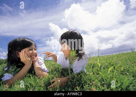 Zwei Mädchen auf der Wiese liegend Stockbild