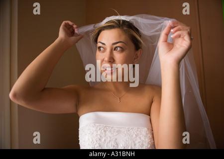 Braut Schleier über Kopf heben und Blick aus Fenster Stockbild