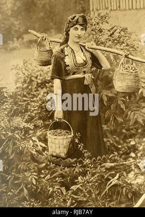 Junge Bäuerin in traditioneller Kleidung mit besticktem Oberteil, Bulgarien. Sie ist die Körbe von Waldbeeren. Stockbild