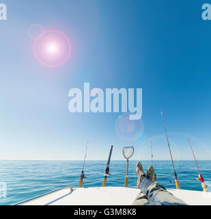 Ruten Angeln und mans Beine auf Segelboot Stockbild
