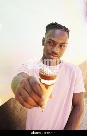 Junge hübsche schwarze Mann trägt ein rosa t-shirt, hält und isst ein Eis im Sommer auf einer bemalten Wand wie ein Sonnenaufgang oder sonnigen Tag Stockbild