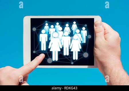 Mann hält einen Tablet-Geräts mit sozialen Medien und Kommunikation Konzept, berühren Sie den Bildschirm mit einem Finger mit blauen Himmel im Hintergrund Stockbild