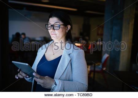 Fokussierte Geschäftsfrau spät in der Digitalen tablet Arbeiten in dunklen Büro Stockbild