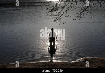 Berlin, Deutschland. 19 Apr, 2019. Ein Mann steht in Sonnenschein in der Schlachtensee. Credit: Christoph Soeder/dpa-Zentralbild/dpa/Alamy leben Nachrichten Stockbild