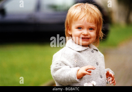Foto von jungen Mädchen außerhalb Lächeln glücklich zu Fuß Kleinkind UK Stockbild