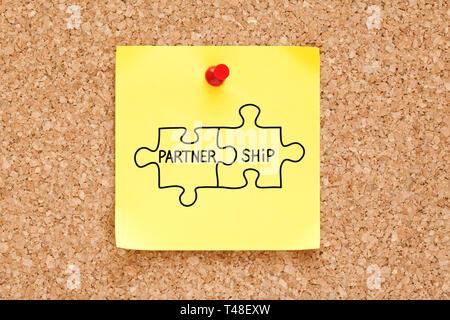 Partnerschaft puzzle Konzept handgeschrieben auf gelbe Haftnotiz auf Bulletin Pinnwand angeheftet. Stockbild
