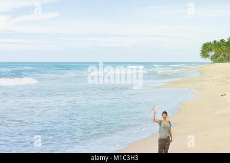 Balapitiya Strand, Sri Lanka - eine junge Frau, die ihre Hand winkend am Strand von Balapitiya Stockbild
