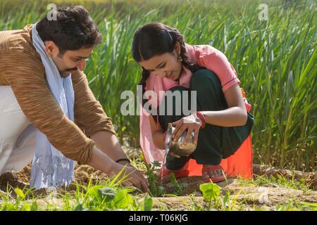 Gerne kleine Mädchen sitzen kleine Pflanzen Bewässerung in der Landwirtschaft Feld zusammen mit ihrem Vater. Stockbild