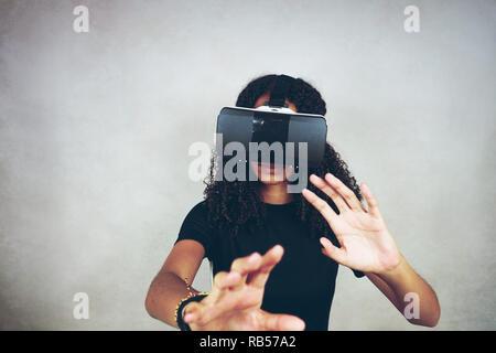 Eine schöne, junge schwarze Frau mit lockiges Afro-Haar seidig trägt Virtual Reality VR-Headset und spielt Videospiele im Studio mit grauem Hintergrund Stockbild
