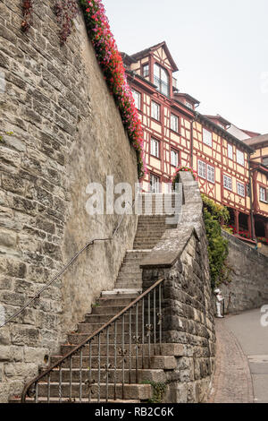 Hohe Steinmauer mit eine lange Treppe zu einigen alten mittelalterlichen Häusern Stockbild