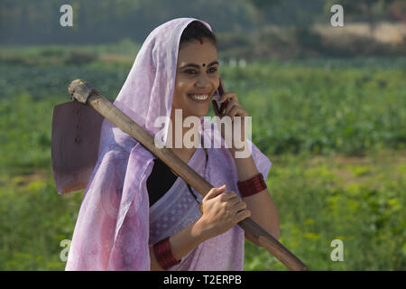 Porträt eines lächelnden Frau, die eine Katze auf der Schulter in einem landwirtschaftlichen Gebiet sprechen über Handy. Stockbild
