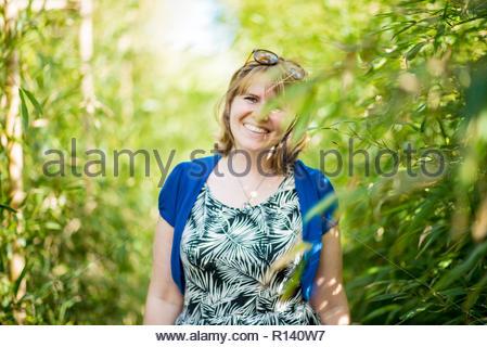 Porträt eines lächelnden jungen Frau, die von Pflanzen Stockbild