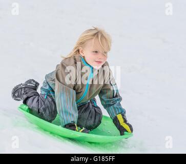 Junge auf Schlitten im Schnee spielen Stockbild