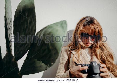Vorderansicht einer Frau mit Sonnenbrille stehen im Freien Stockbild
