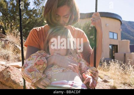 Eine Mutter und Tochter auf einer Schaukel zusammen Stockbild