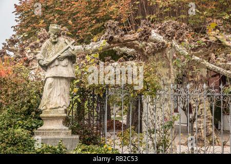 Steinerne Statue mit farbigen Blätter eines Baumes und Efeu Stockbild