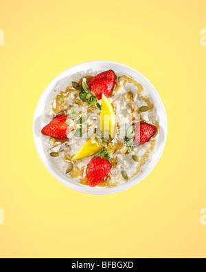 Porridge mit Mango, Erdbeeren, Honig und Kürbis Samen, Frühstück von 07:00 anzeigt. Stockbild