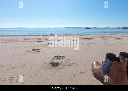 Ein paar Schuhe stehen auf dem Strand Stockbild