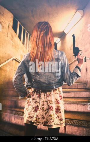 Rückansicht einer rothaarigen Frau auf eine Waffe am Eingang von einer u-Bahn Stockbild