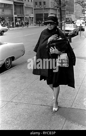 Manhattan Straße Szene der 60er Jahre Mode ältere modisch gekleidete Frau trägt einen Union Jack Flagge hand Tasche, als Sie zu einem Termin eilt. 1969 60 s USA UNS HOMER SYKES Stockbild