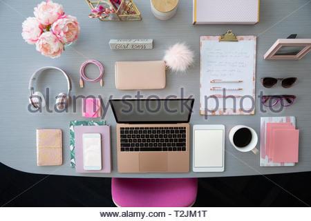 Ansicht von oben pinkfarbener Laptop und Bürobedarf auf Schreibtisch Stockbild