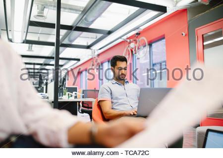 Konzentrierte Geschäftsmann am Laptop arbeiten in Coworking Space Stockbild