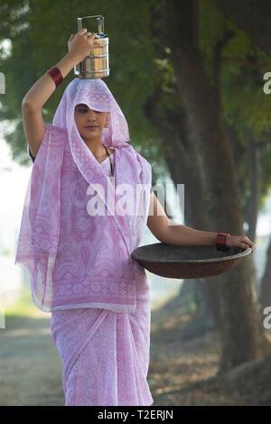 Ländliche Frau oder tageslohn Arbeiter in Saree tragen ein Bügeleisen Gold Pan in der Hand und einem Tiffin box auf den Kopf zu arbeiten. Stockbild