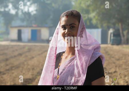 Porträt einer Frau, die den ländlichen Raum in einem landwirtschaftlich genutzten Gebiet mit dem Kopf unter die Sari. Stockbild