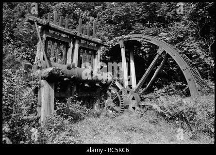 Zinn Briefmarken, Trelocke Farm, Nancledra, Ludgvan, Cornwall, Cornwall, 1967-1970. Zinn Briefmarken und Wasserrad auf Land an Trelocke Bauernhof (aka Schloss Hof). Die Stempel und der waterwheel, die die Energie zur Verfügung gestellt, wurden verwendet, um Zinnerz aus Abfällen Rock in der Nähe von Mülldeponien gebracht zu hämmern. Sie wurden zu Geevor Mine Museum im Jahr 1983 verschoben. Stockbild