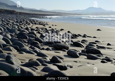 Famara Strand mit schwarzem Lavagestein Felsbrocken abgerundet und durch Wellengang, Lanzarote, Kanarische Inseln, Februar geglättet. Stockbild