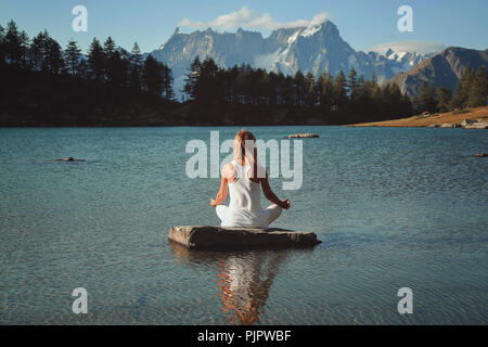 Frau Meditation in Mountain Lake. Lotus Asana Stockbild