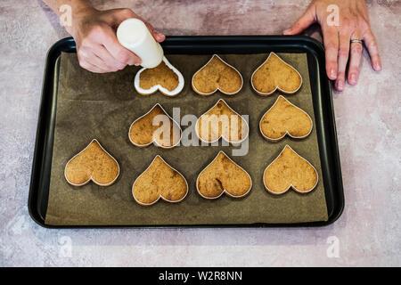 Hohen Winkel in der Nähe der Person verzieren frisch gebackene Hart-förmige Cookies mit paspeliertem weiße Zuckerglasur, überschwemmung Vereisung Technik. Stockbild
