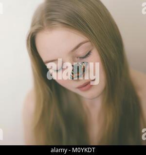 Schmetterling auf der Nase der kaukasischen Jugendmädchen Stockbild
